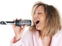 Woman singing with hairbrush Royalty Free Stock Image