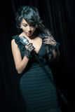 Woman singing jazz. Young woman with a retro microphone wearing black dress singing jazz in a club scene. Emotional female singing stock photo