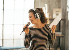 Woman singing karaoke in loft apartment Stock Photography