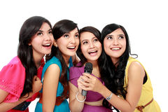 Woman singing karaoke together. Four beautiful stylish women singing karaoke together isolated over white background Stock Image
