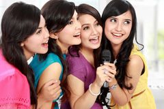 Woman singing karaoke together. Four beautiful stylish women singing karaoke together Royalty Free Stock Photos