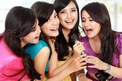 Woman singing karaoke together. Four beautiful stylish women singing karaoke together Stock Photo