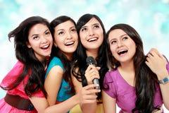 Woman singing karaoke together. Four beautiful young women singing karaoke together Royalty Free Stock Photos