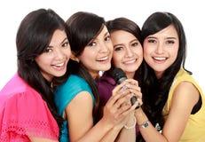 Woman singing karaoke together. Four beautiful young women singing karaoke together Royalty Free Stock Photo
