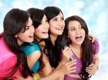Woman singing karaoke together. Four beautiful young women singing karaoke together Royalty Free Stock Image
