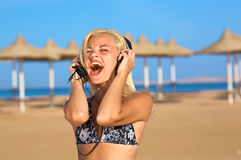 Woman singing loudly. A view of a young woman singing loudly with the music she hears in her earphone Stock Image