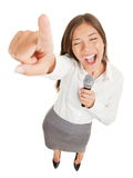 Woman singing or making a point. Fun high angle view of a passionate attractive young woman holding a microphone singing or making a point during a speech royalty free stock image