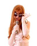Woman singing with microphone. Young pretty woman singing with microphone isolated Stock Image