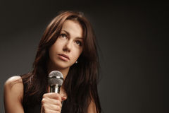 Woman singing into microphone Royalty Free Stock Photo