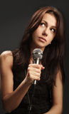 Woman singing into microphone Royalty Free Stock Images