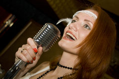 Woman singing into microphone Royalty Free Stock Photos