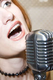Woman singing into microphone Royalty Free Stock Image