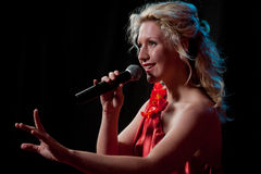 Woman singing in microphone. Pretty woman singing in microphone over the black background Royalty Free Stock Photos