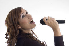 Woman singing in microphone Stock Photos
