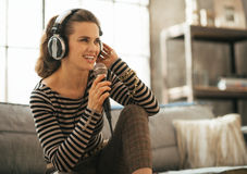 Woman singing with microphone in loft apartment Royalty Free Stock Photos