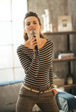 Woman singing with microphone in loft apartment Stock Images