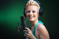 Woman singing on microphones Stock Photos