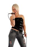 Woman singing into microsphone. Sexy blond woman singing into a microphone Royalty Free Stock Images