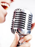 Woman singing on retro microphone Royalty Free Stock Images
