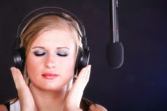 Woman singing rock song microphone headphones Royalty Free Stock Image