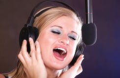Woman singing rock song microphone headphones Stock Photos