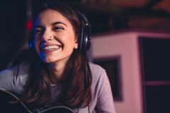 Woman singing a song in recording studio. Smiling woman singing a song in recording studio. Female singer with guitar singing a song royalty free stock images