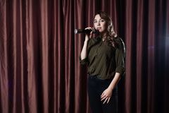 Woman singing on stage in the microphone karaoke on the background of red curtains stock images