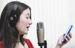 Woman singing at a studio microphone, wearing a headphone and re. Ading the song lyrics on the phone. White background Stock Image