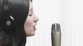 Woman singing at a studio microphone, wearing a headphone.  Stock Photos