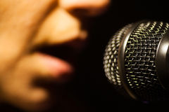 Woman singing to microphone. Close up image of a woman singing to a microphone stock images