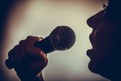Woman singing to microphone. Close up image of a silhouette of a woman singing to a microphone royalty free stock photography