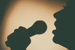 Woman singing to microphone Royalty Free Stock Image