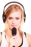 Woman singing to microphone wearing headphones Royalty Free Stock Photos