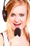 Woman singing to microphone wearing headphones Royalty Free Stock Images