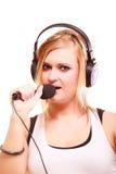 Woman singing to microphone wearing headphones Stock Photos
