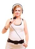 Woman singing to microphone wearing headphones Royalty Free Stock Image