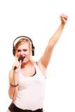 Woman singing to microphone wearing headphones Royalty Free Stock Photo