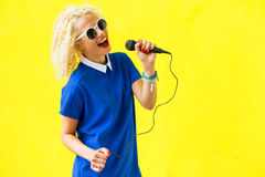 Woman singing and using microphone Stock Photo