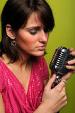 Woman Singing into Vintage Microphone Royalty Free Stock Images