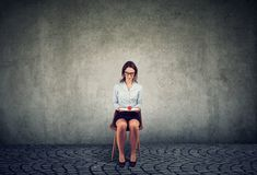 Woman with single tomato sitting on chair royalty free stock images