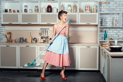 Woman sings and cleans the house. stock photos