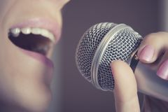 A woman sings into a microphone at a recording studio, her mouth close up. A woman sings into a microphone at a recording studio, her mouth close up royalty free stock photos