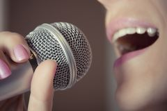 A woman sings into a microphone at a recording studio, her mouth close up. Stock Images