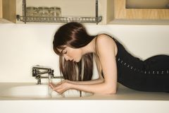 Woman at sink. Royalty Free Stock Photo