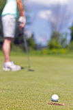 Woman sinking a putt on a golf green - selective focus. Woman putting the golf ball into the cup Stock Photo
