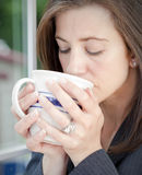 Woman sipping coffee Stock Images