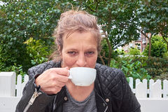 Woman sipping coffee in a garden Stock Image