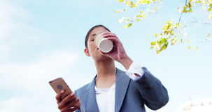 Woman sipping coffee outside and using smartphone stock video footage