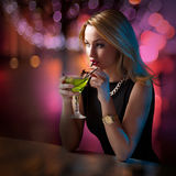 Woman sipping her cocktail while looking around Stock Photos