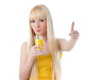Woman sipping orange juice and giving thumbs up Royalty Free Stock Images